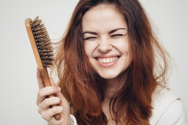 Счастливая женщина с щеткой для волос и здоровыми волосами.