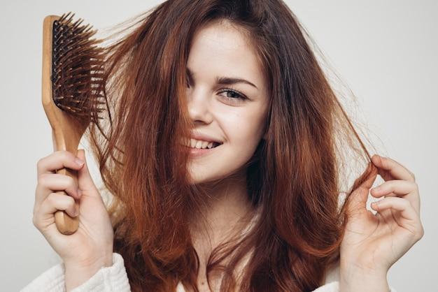 Счастливая женщина с расческой на светлых и здоровых волосах