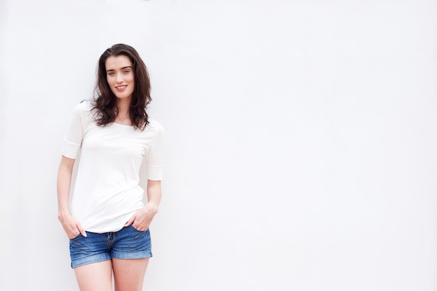 Happy woman with hands in pockets against white background
