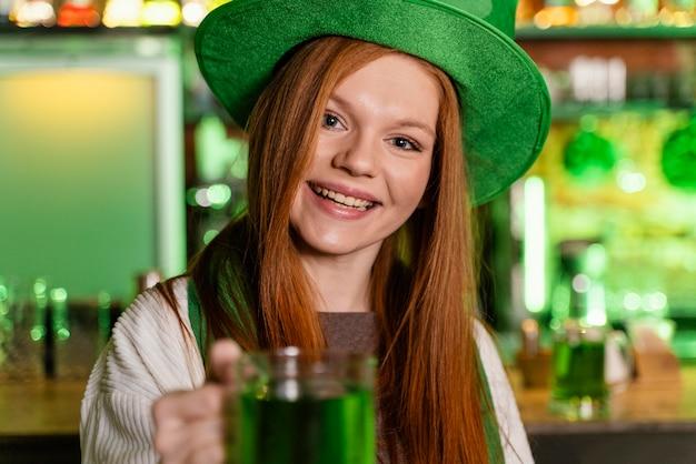 Счастливая женщина в шляпе празднует ул. день патрика в баре с напитком