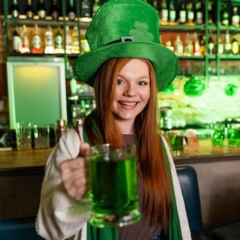Счастливая женщина в шляпе празднует ул. день патрика в баре