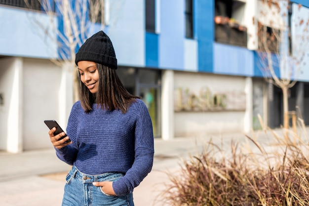 Happy woman with hat in city street, while using technology outdoors, holding cell phone. she is black, on her early twenties