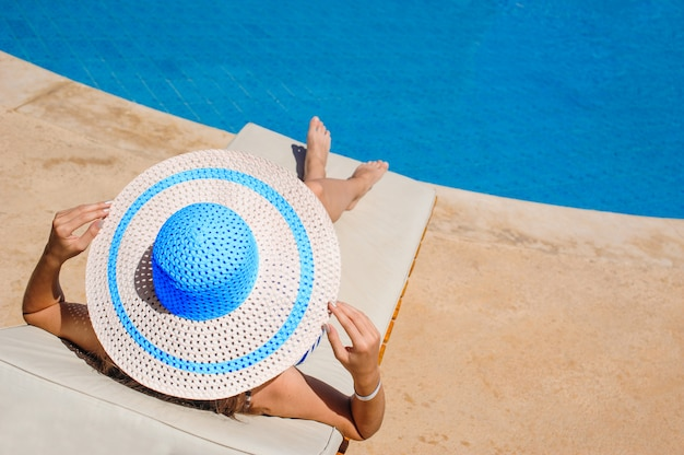 Happy woman with hat sunbathing on a sun lounger by the pool