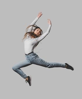공중에서 점프하는 헤드폰으로 행복 한 여자