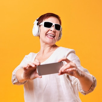 Happy woman with headphones and phone mock-up