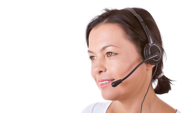 白い背景の上のコールセンターで働くヘッドセットを持つ幸せな女性
