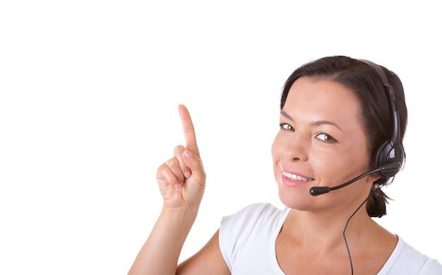 Счастливая женщина с гарнитурой, работающая в callcenter, показывает направление пальца к copyspace для вашего дизайна на белом фоне