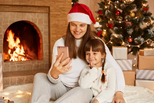 Happy woman with her cute little daughter sitting on floor near christmas tree and fireplace, holding smart phone, looking at device screen, having positive facial expressions and festive mood.