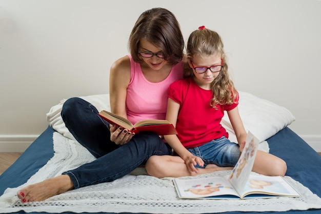 Happy woman with her daughter child, reading together