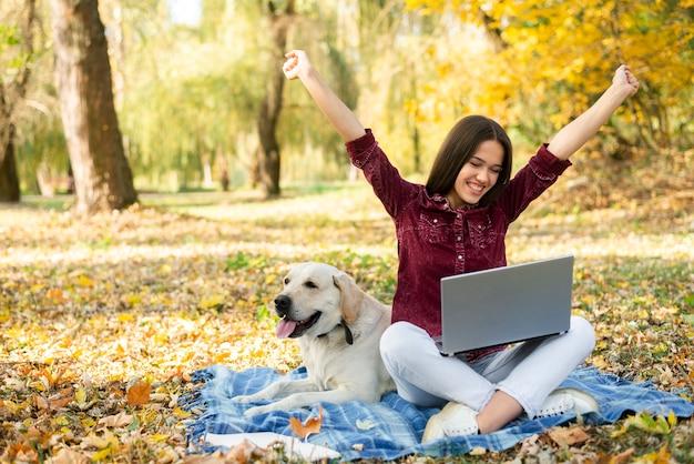 公園で彼女の犬と一緒に幸せな女