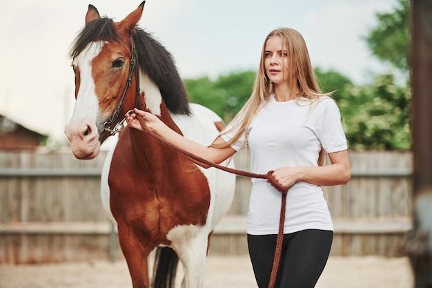 Счастливая женщина со своей лошадью на ранчо в дневное время.
