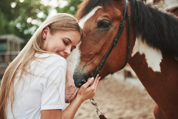 Happy woman with her horse on the ranch at daytime.