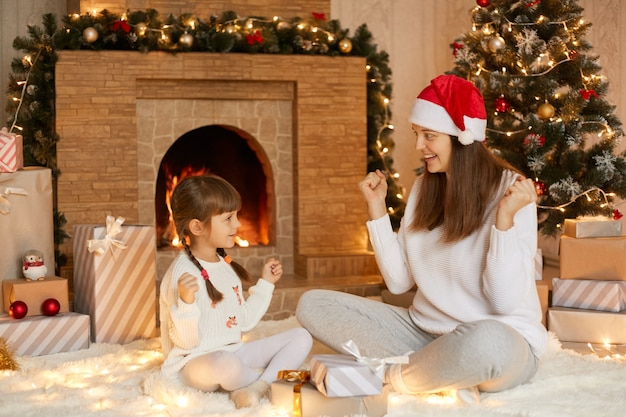 Happy woman with her little daughter sitting in living room near christmas tree