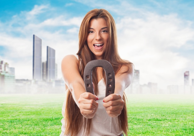 Happy woman with horseshoe over cityscape