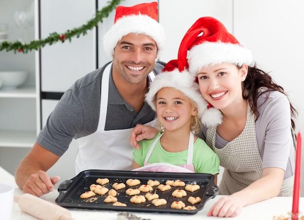 夫と娘とビスケットを準備している幸せな女性