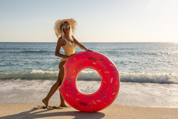 Счастливая женщина с надувным пончиком на тропическом пляже.