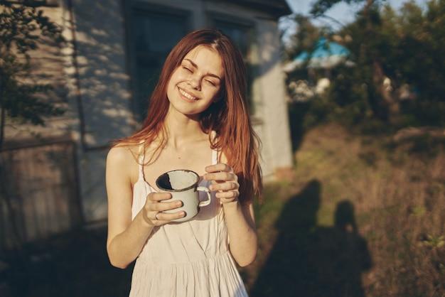 Счастливая женщина с кружкой железа на открытом воздухе в саду возле легкого здания.
