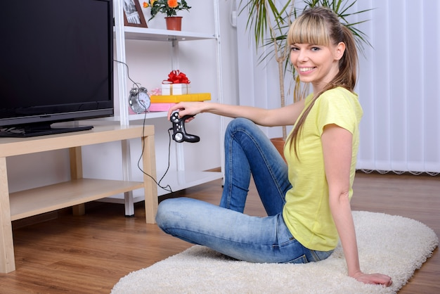 Happy woman with joystick playing video games at home.
