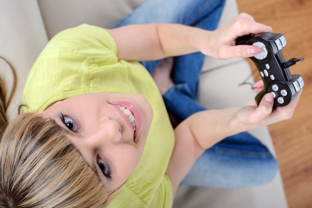 Happy woman with joystick playing video games.