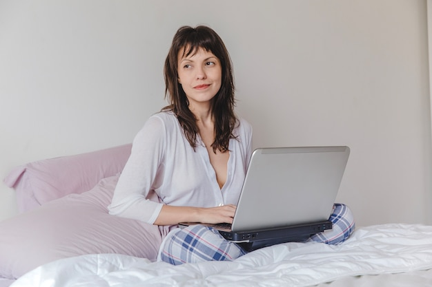 Happy woman with laptop on bed