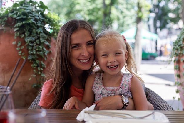 카페테리아의 여름 테라스에 있는 테이블에 작은 금발 소녀와 함께 행복한 여자.