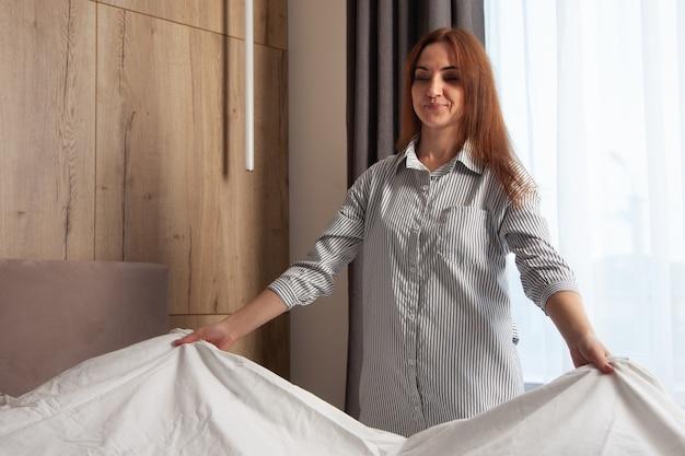 Счастливая женщина с длинными рыжими волосами раскладывает комплект постельного белья на кровати комнаты с копией пространства. производство органического текстиля. белье декорировано полосами в виде клетки. подушки разные