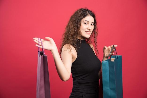 赤のバッグの多くを持つ幸せな女