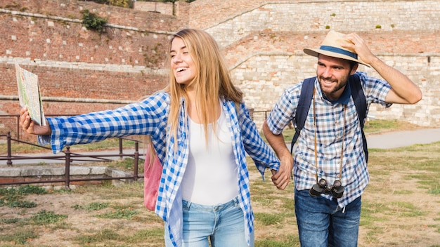 Happy woman with map holding boyfriend's hand