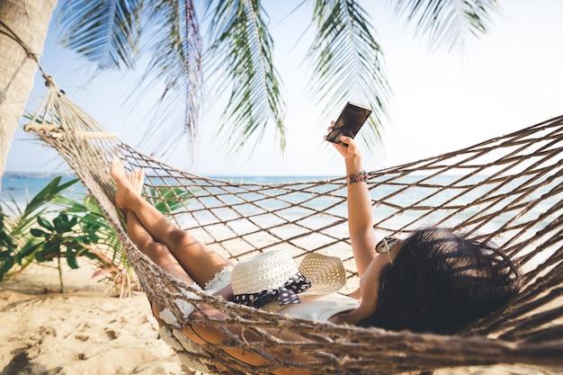 携帯電話で幸せな女はハンモックでリラックスします。
