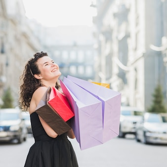 Happy woman with multi colored shopping bags