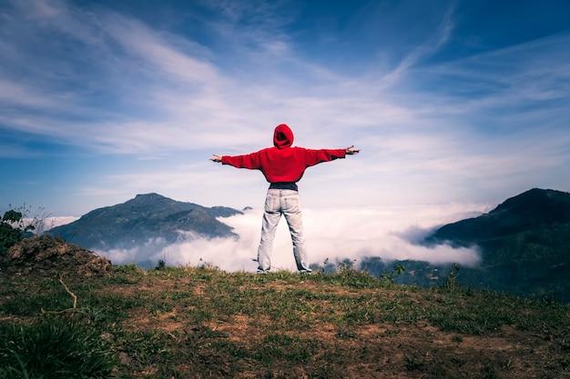 両手を広げて幸せな女性は、成功、自由、明るい未来を楽しんで、明るい空の下で山の崖の端の頂上にとどまります。飛行の効果。旅行と幸福の概念。