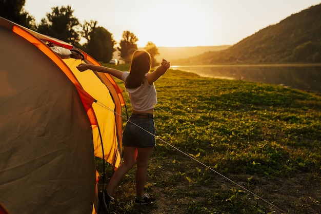 Happy woman with open arms stays near the tent around the mountains under the sunrise sky enjoying leisure and freedom.