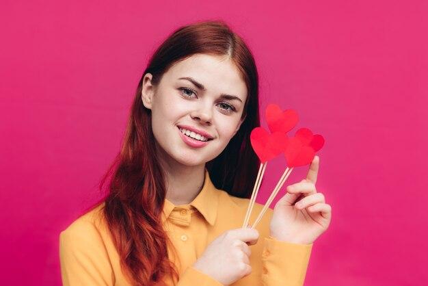 スティックピンクのバレンタインデーに紙の心を持つ幸せな女性