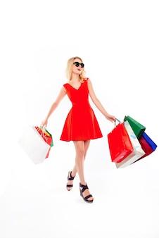 白いスペースで買い物をした後、紙袋を持つ幸せな女性