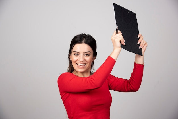 회색 배경에 펜과 클립보드를 가진 행복한 여자.
