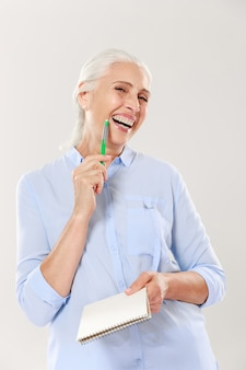Happy woman with pen and notebook looking and smiling