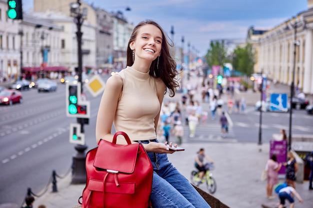 Счастливая женщина с телефоном и рюкзаком сидит возле улицы с движением