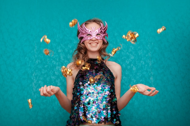 Happy woman with pink mask and golden confetti