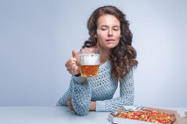 ピザとビール、テキスト用のスペース、灰色の空間で幸せな女