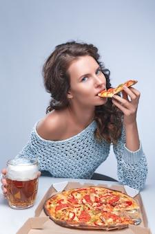 Счастливая женщина с пиццей и пивом на сером пространстве, место для текста