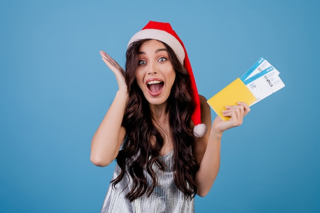Happy woman with plane tickets and passport wearing santa hat