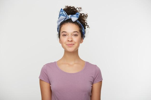 캐주얼 티셔츠와 세련된 머리띠를 입은 긍정적 인 표현으로 행복한 여자