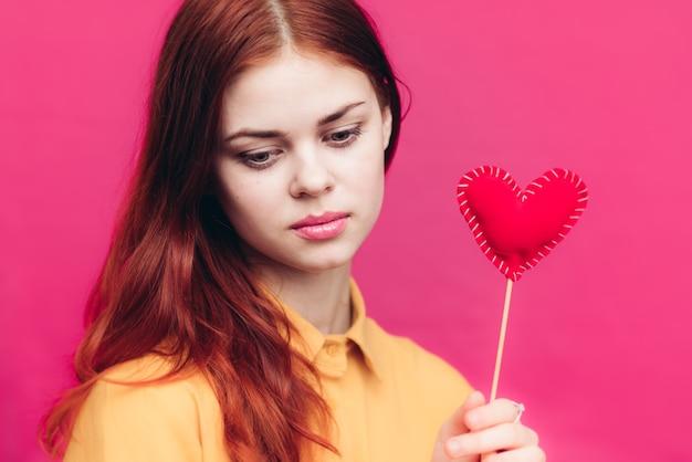 ピンクと黄色のシャツのスティックに赤いハートの幸せな女