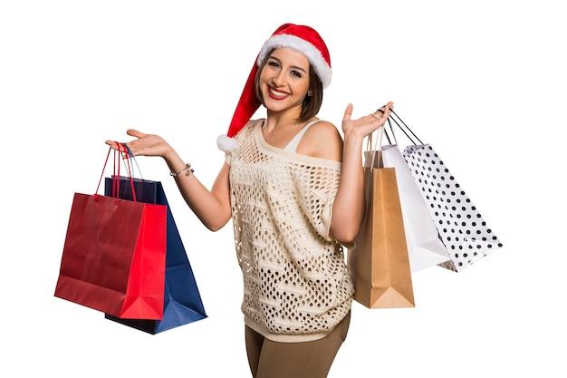 Счастливая женщина с шляпой санта, держа хозяйственные сумки. рождественские покупки