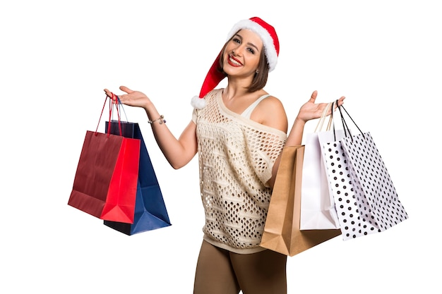 Happy woman with santa hat holding shopping bags. christmas shopping