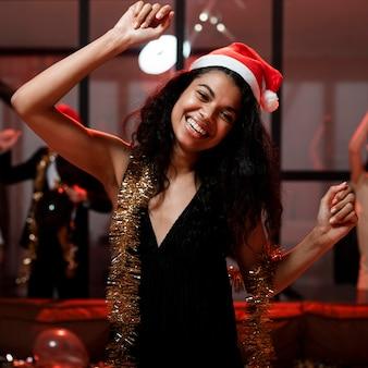 Счастливая женщина с вечеринкой в шляпе санта-клауса