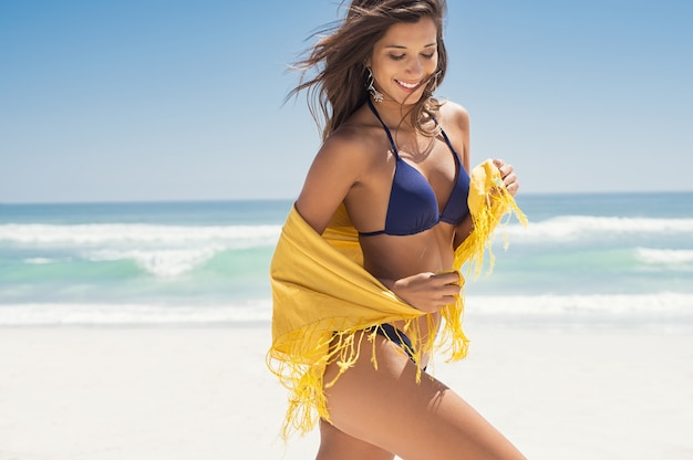 Happy woman with scarf at beach