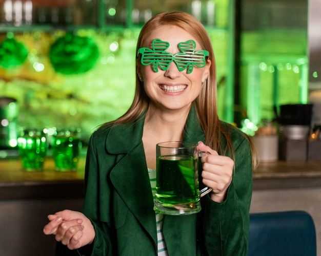 Happy woman with shamrock glasses celebrating st. patrick's day at the bar with drink