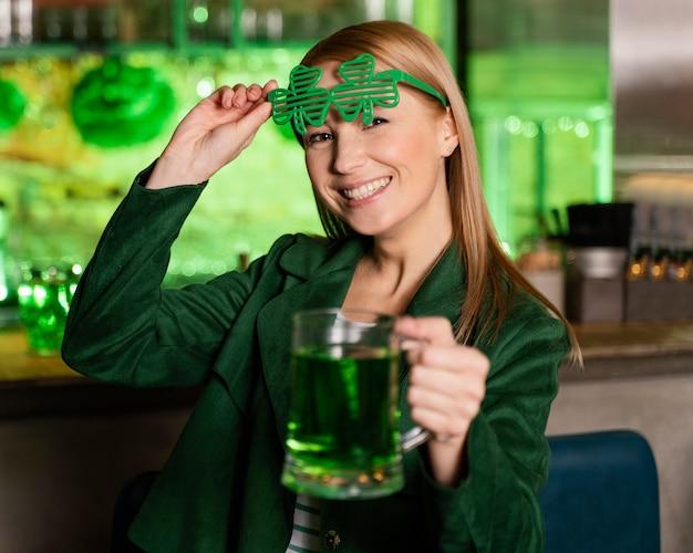 Счастливая женщина в очках трилистника, празднуя ул. день патрика с напитком в баре