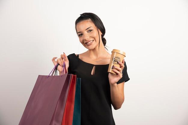 ショッピングバッグと白い壁にポーズをとってコーヒーと幸せな女性。